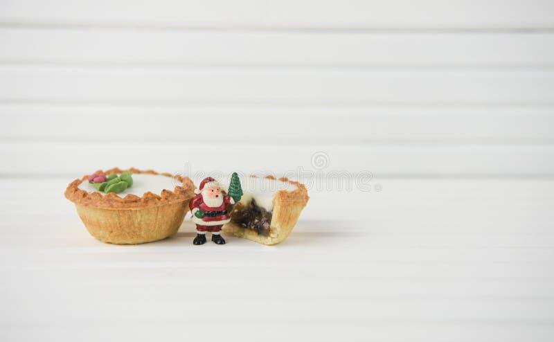 Het beeld van de Kerstmisfotografie van Kerstmisvoedsel hakt pastei en de minikerstman op witte houten achtergrond fijn royalty-vrije stock foto's
