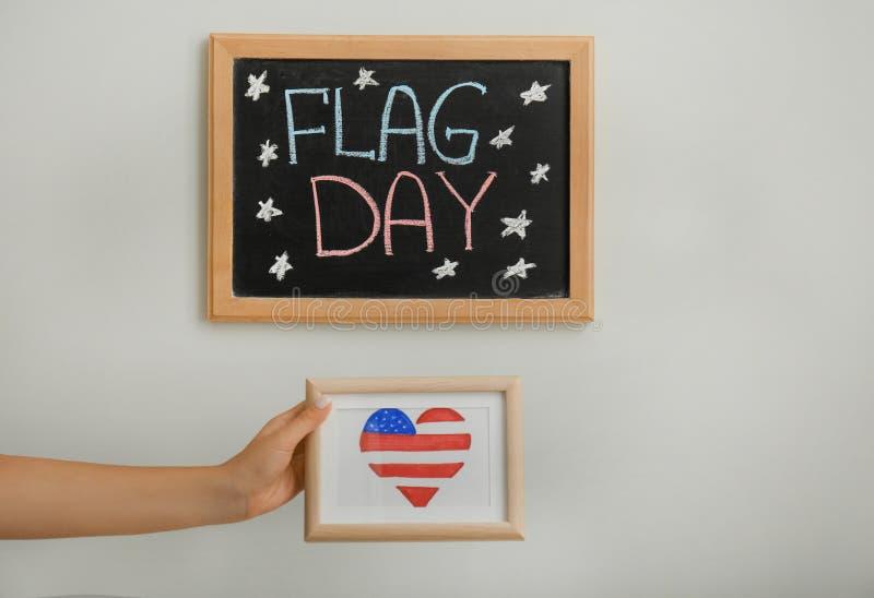 Het beeld van de vrouwenholding met hart vormde tekening van Amerikaanse nationale vlag op lichte achtergrond stock foto's