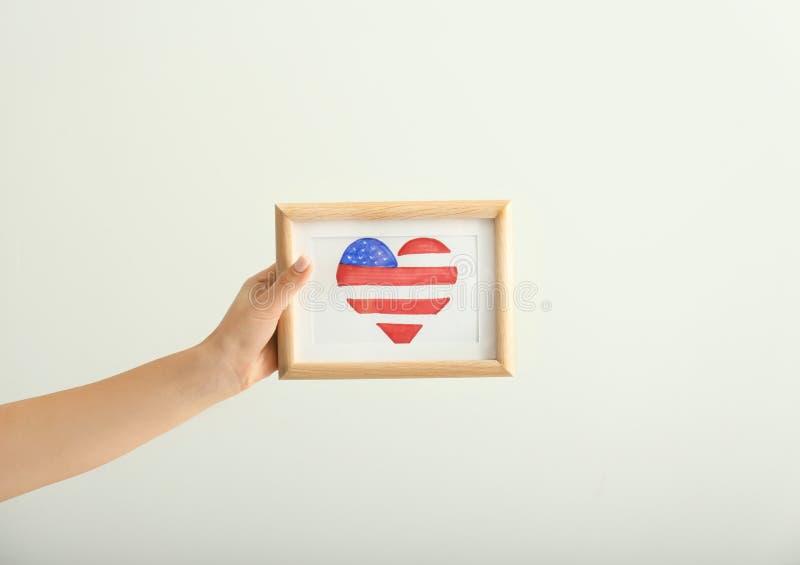 Het beeld van de vrouwenholding met hart vormde tekening van Amerikaanse nationale vlag op lichte achtergrond stock foto