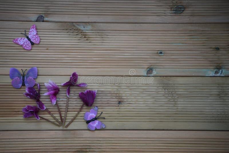 Het beeld van de de winterfotografie van roze purpere cyclaam bloeit en pretstuk speelgoed vlinders op rustieke houten achtergron royalty-vrije stock foto's