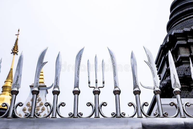 Het beeld van decoratieve scherpe zwaarden, drietand en spear ijzer perkt Aziatische stijl met pagodeachtergrond in in tempel van stock foto's
