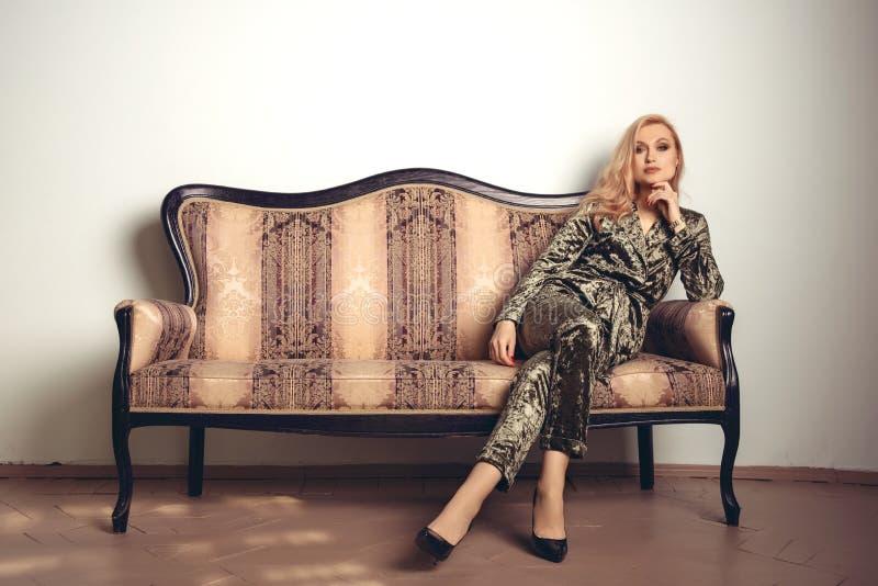 Het beeld van een mooie luxueuze vrouwenzitting op een uitstekende laag stock fotografie