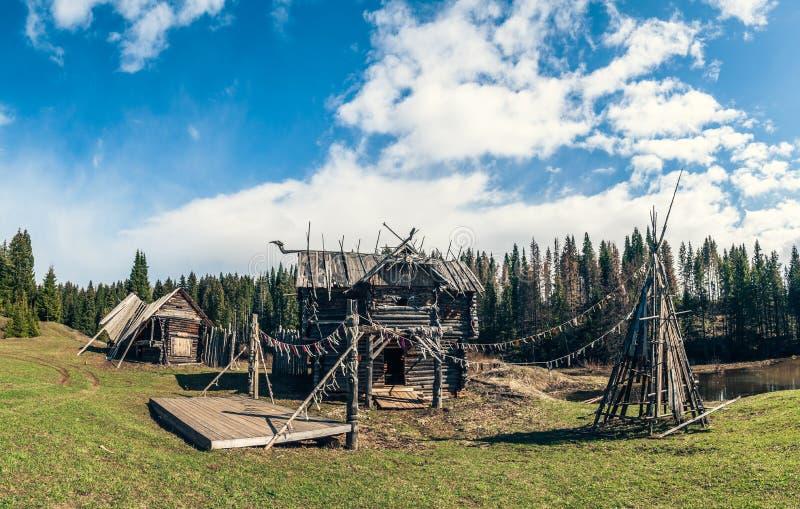 Het beeld van een oude verlaten houten nederzetting, verlicht door de middagzon tegen een heldere blauwe hemel stock foto's