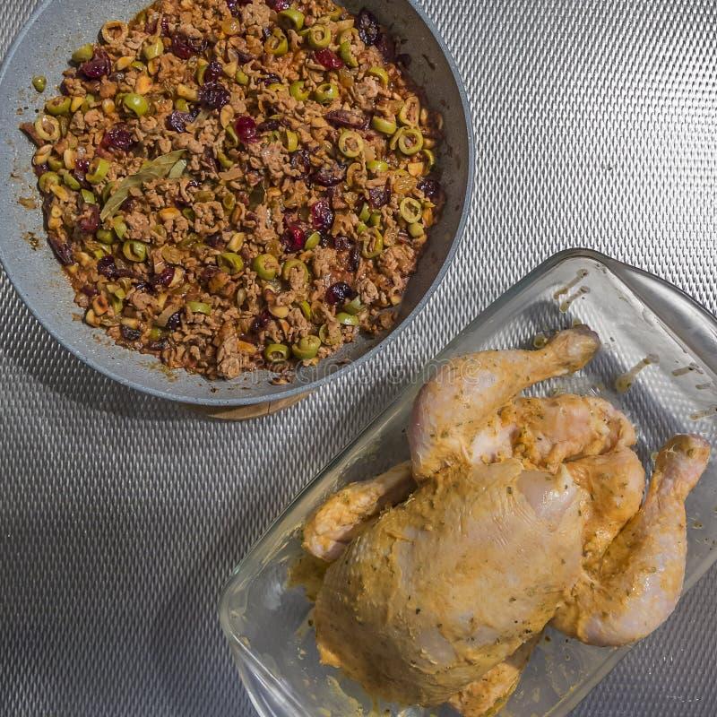 Het beeld van een ruwe kip slathered met boter en naast het is het vullen van reeds gekookt gehakt stock afbeelding