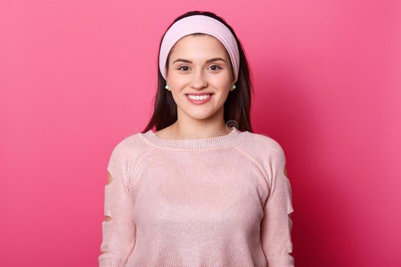 Het beeld van Europese mooie vrouw met donker haar, draagt toenam sweater Dame die in goede stemming zijn terwijl het stellen all stock fotografie