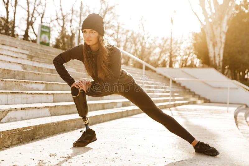 Het beeld van gehandicapt atletisch meisje in sportkleding, het doen zit UPS en royalty-vrije stock fotografie