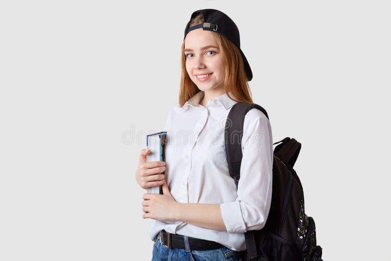 Het beeld van gelukkige Kaukasische student met rugzak en groot boek, gekleed overhemd, de rug van het jeansvizier GLB, bevindt z royalty-vrije stock afbeelding