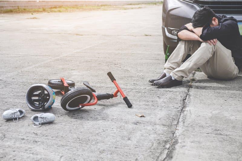 Het beeld van geschokte en doen schrikken bestuurder na ongeval impliceerde de fiets en de helm van het Jonge geitje liggend op d royalty-vrije stock fotografie
