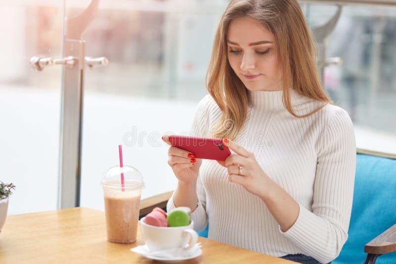 Het beeld van jong knap blondewijfje zit in koffie, neemt foto van haar diner met haar telefoon, eet kleurrijke makarons en stock afbeelding