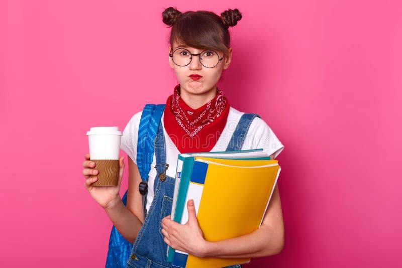 Het beeld van het jonge mooie klembord van de studentenholding en de koffie vormen terwijl het denken over haar rapport, voelen t stock afbeeldingen