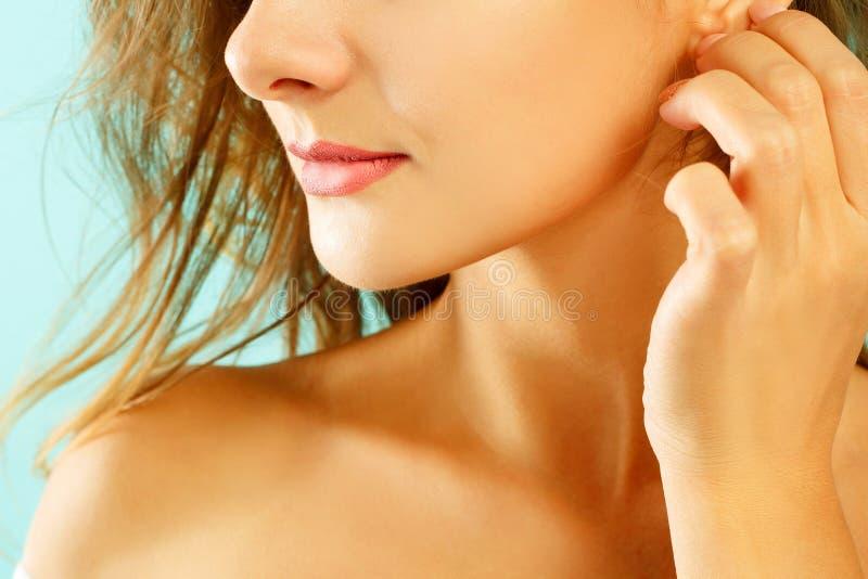 Het beeld van jonge vrouwen` s lippen sluit omhoog het tauching van haar oor over blu royalty-vrije stock afbeeldingen