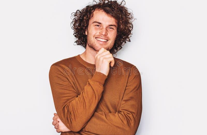 Het beeld van Kaukasisch mannetje met krullend haar die en voor reclame glimlachen stellen draagt bruine die trui, op witte muur  stock afbeelding