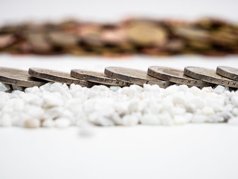 Het beeld van lijn van twee Euro muntstukken op witte kleine stenen sluit omhoog stock fotografie