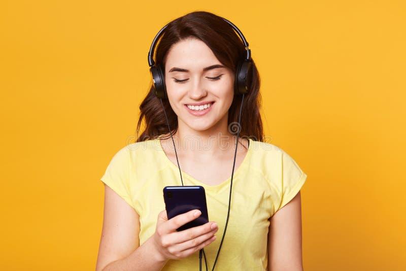 Het beeld van mooi donker haired meisje in toevallig overhemd ontspant met favoriete muziek Binnenportret die van scaucasian wijf royalty-vrije stock foto