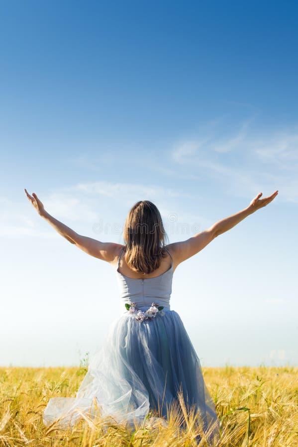 Het beeld van mooie blonde jonge vrouw die lange blauwe balkleding met brede wapens draagt breidt het kijken omhoog op tarwegebie stock foto