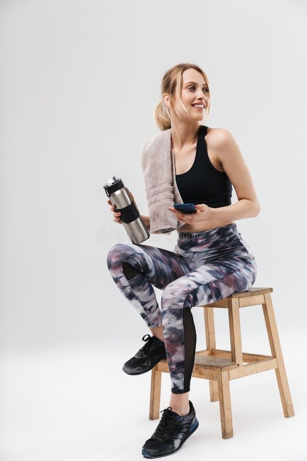 Het beeld van mooie blonde vrouwenjaren '20 kleedde zich in sportkleding met handdoek over halszitting op stoel na training in gy stock fotografie