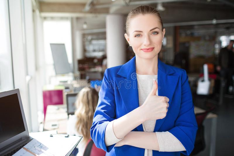 Het beeld van Nice van meisje in het blauwe kostuum glimlachen Zij houdt één hand op haar heupen en een andere op het jasje Meisj stock afbeelding