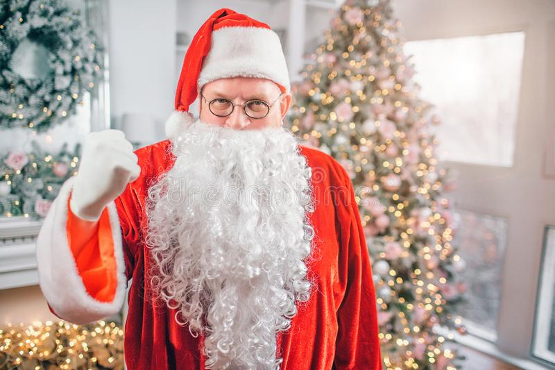 Het beeld van Santa Claus bevindt zich en kijkt op camera Hij toont de vuistmens dreigt Hij is in feestelijke ruimte royalty-vrije stock afbeeldingen