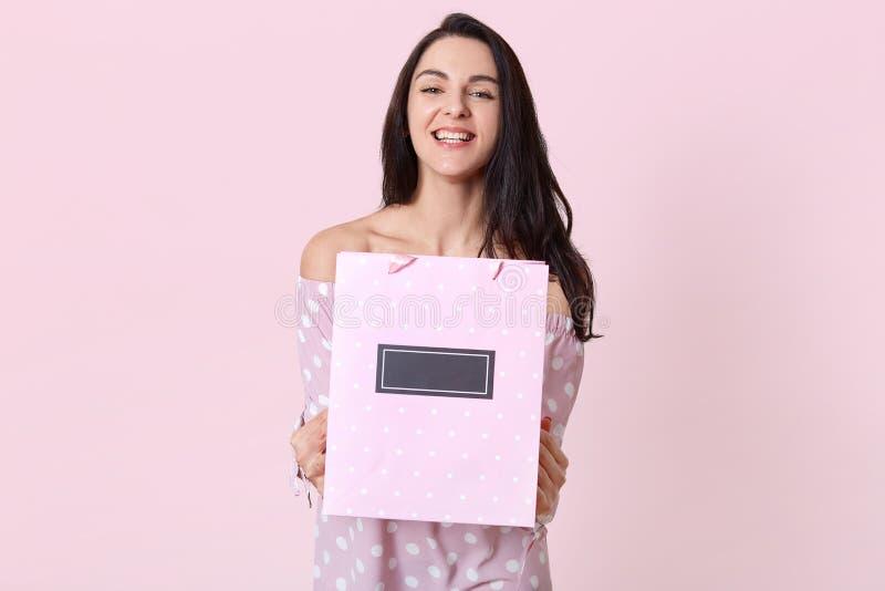 Het beeld van tevreden jonge Kaukasische vrouw houdt giftzak met lege ruimte, glimlacht ruim bij camera, ontvangt heden op verjaa royalty-vrije stock foto