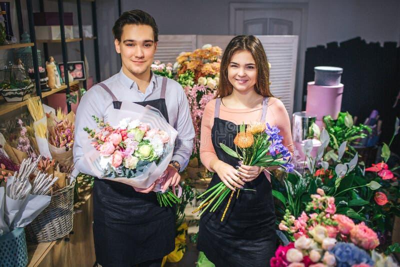Het beeld van twee bloemistentribune en kijkt op camera Zij houden boeketten van bloemen en glimlach De verkopers zijn vrolijk stock afbeeldingen