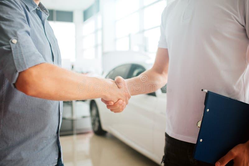 Het beeld van twee jonge mensen het schudden dient voorzijde van witte auto in Zij maakten een overeenkomst De klant en de verkop royalty-vrije stock foto