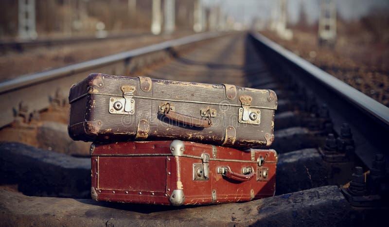 Het beeld van twee uitstekende koffers op spoorwegsporen royalty-vrije stock afbeelding
