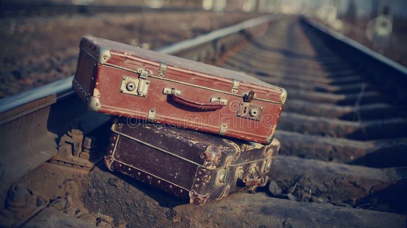 Het beeld van uitstekende koffers die op spoorwegsporen worden geworpen stock afbeeldingen