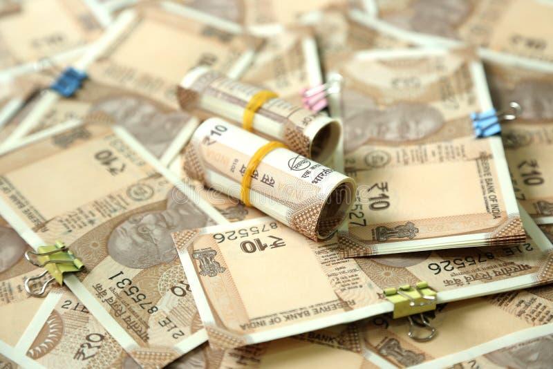 Het beeld van verspreide Indische munt neemt nota en rolt van de nota van de 10 Roepiemunt