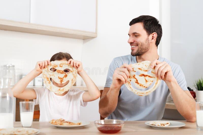 Het beeld van vrolijk klein meisje behandelt gezicht met pannekoek, zit dichtbij haar hartelijke vader bij keuken, heeft smakelij stock afbeeldingen