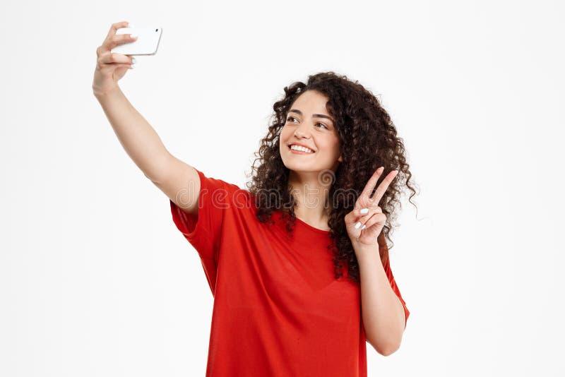 Het beeld van vrolijk krullend meisje maakt selfie stock fotografie
