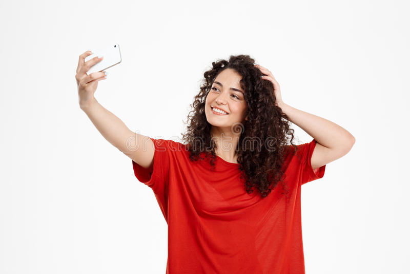 Het beeld van vrolijk krullend meisje maakt selfie royalty-vrije stock fotografie