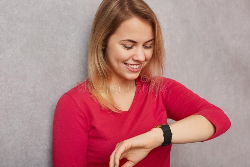 Het beeld van vrolijke blondevrouw bekijkt positief polshorloge, controleert tijd, verheugt zich het hebben van vrije tijd vóór b stock fotografie