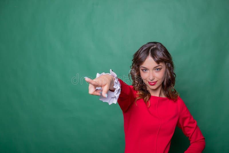 Het beeld van vrolijke vrouw met lang bruin haar die en wijsvinger opzij hey betekenen tonen u isoleerde over groen knipogen royalty-vrije stock foto