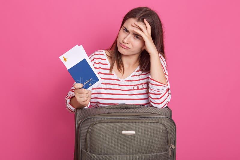 Het beeld van vrouw die in gestreept overhemd over roze achtergrond, dichtbij haar koffer zitten, die documenten in handen houden stock fotografie
