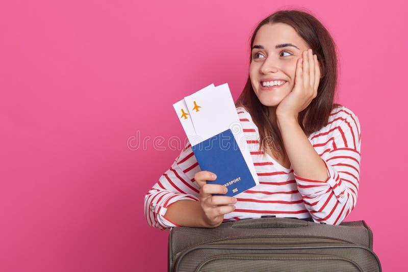 Het beeld van vrouw in gestreepte van het overhemds holdingh paspoort en vliegtuig kaartjes, zit dichtbij koffer, dromend over to stock foto's