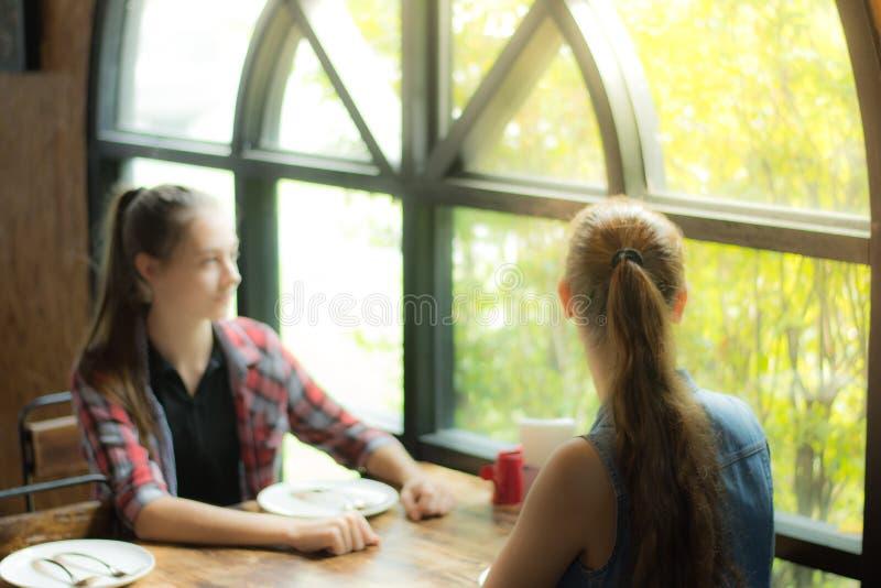 Het beeld vertroebelde voor achtergrond twee jonge vrouwenzitting die bij de lijst op haar maaltijd wachten Glimlachend meisje di stock foto