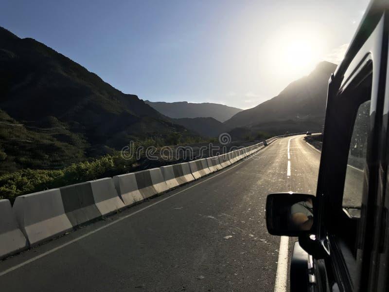 Het beeld voor de sportwagenscène erachter als zon die met windturbines dalen in de rug stock illustratie