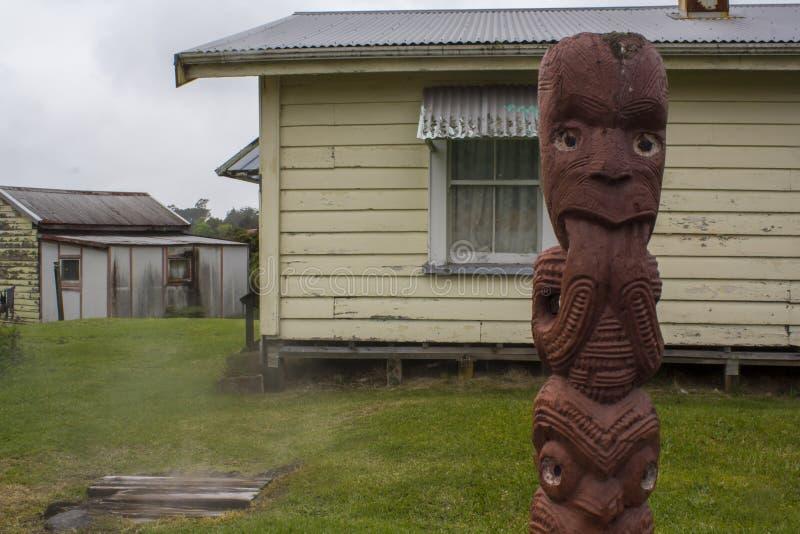Het beeldhouwwerk en de huizen van Maori Wood Carving op achtergrond stock foto's