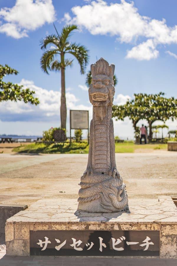 Het beeldhouwwerk van de de draaksteen van Okinawanryukyu op het zonsondergangstrand in de Amerikaanse Dorpsbuurt van Chatan-Stad stock fotografie