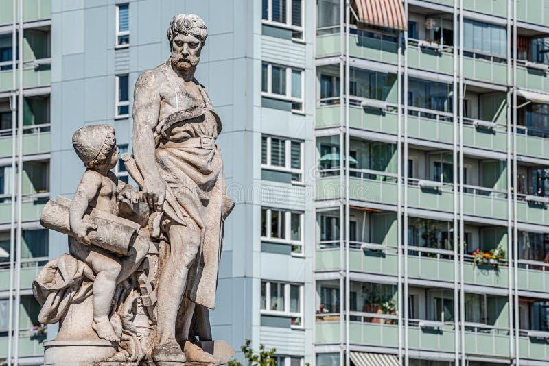 Het beeldhouwwerk van ingenieur en geleerde op Zoll-Brug in Maagdenburg en multistore de bouw op achtergrond, Duitsland, stellen  royalty-vrije stock fotografie