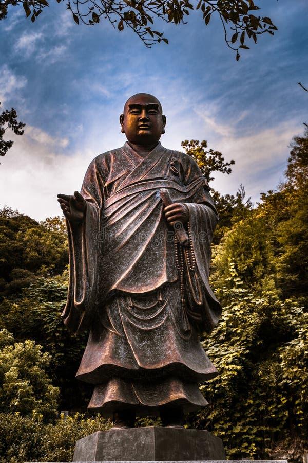 Het beeldhouwwerk van Kamakurabuddah dat over het kerkhof en de tempel kijkt stock foto's