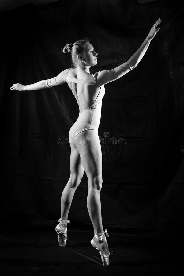 Het beeldsilhouet van mooie jonge dame in het dansen stelt op zwarte achtergrond stock afbeeldingen