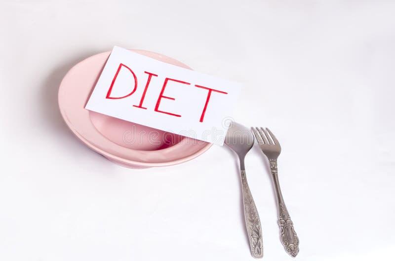 Het begrip gewichtsverlies, op een witte achtergrond, een lege plaat met voorzieningen en het inscriptie dieet royalty-vrije stock afbeeldingen