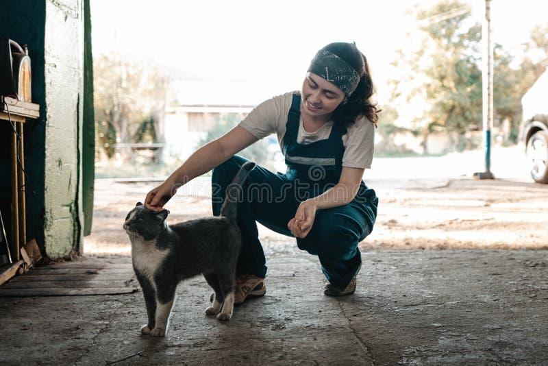 Het begrip kleine onderneming, feminisme en gelijkheid van vrouwen Een jonge vrouwelijke auto-monteur beroert een kat, op de acht stock afbeeldingen