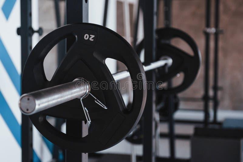 Het begrip sterkte Zwarte barbel op de metalen standaard in de gymzaal overdag Geen mensen rond stock afbeeldingen