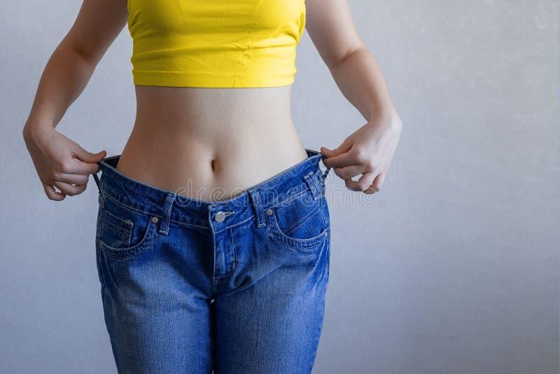 Het begrip voeding en gewichtsverlies Een vrouw in grote jeans op een blauwe achtergrond laat haar slanke maag zien Liposuctie stock foto's