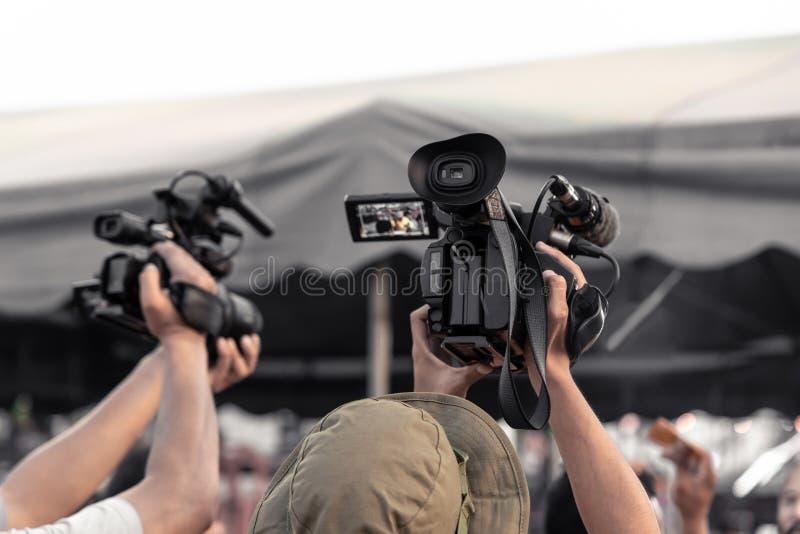 Het behandelen van gebeurtenis met een professionele videocamera Videographer die met materiaal werken royalty-vrije stock foto's