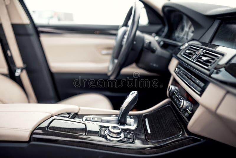 Het beige en zwarte binnenland van moderne auto, close-updetails van automatisch transmissie en toestel plakt tegen stuurwielbede stock foto
