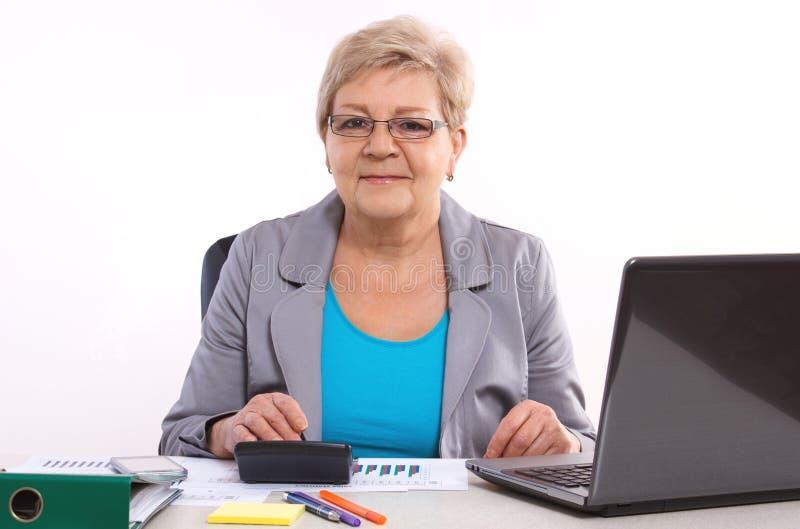Het bejaarde bedrijfsvrouw werken bij haar bureau in bureau, analyse van verkoop plant, bedrijfsconcept stock foto's