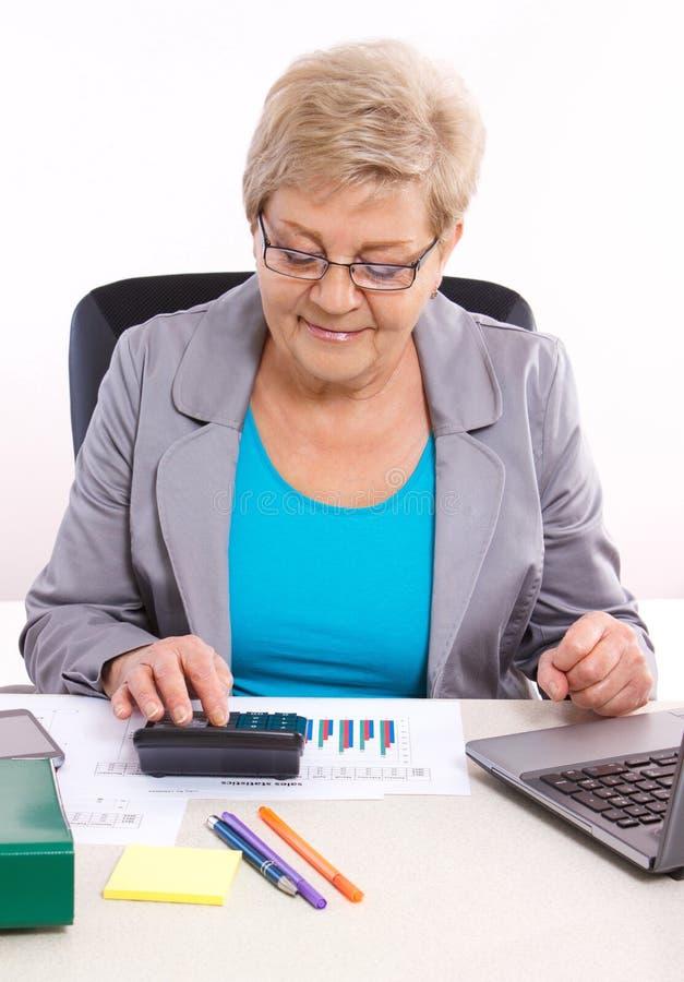 Het bejaarde bedrijfsvrouw werken bij haar bureau in bureau, analyse van verkoop plant, bedrijfsconcept stock foto